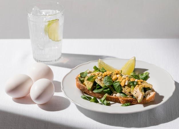 Wysoki kąt tostu z awokado na talerzu ze szklanką lodowatej wody i jajkami