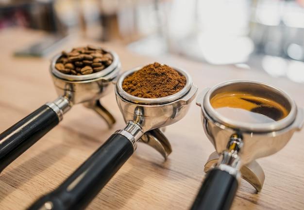 Wysoki kąt trzech filiżanek ekspresów do kawy z różnymi etapami kawy