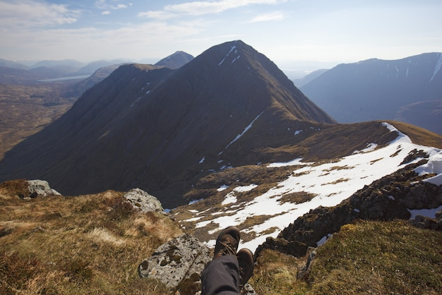 Wysoki kąt ujęcia nóg człowieka siedzącego na ziemi u szczytu gór