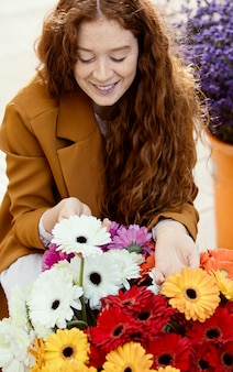 Wysoki kąt uśmiechnięta kobieta na zewnątrz wiosną z bukietem kwiatów