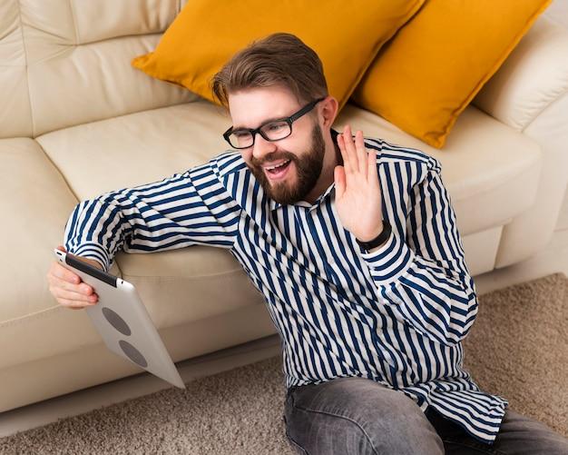 Wysoki kąt uśmiechniętego człowieka w domu z tabletem