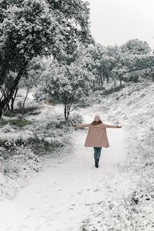 Wysoki kąt widok z tyłu anonimowej kobiety idącej z wyciągniętymi ramionami wzdłuż zaśnieżonej ścieżki i cieszącej się spacerami po lesie w zimie