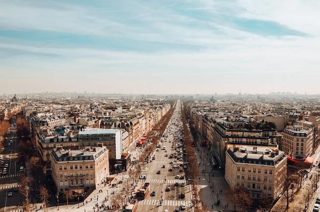 Wysoki kąt widzenia avenue des champs-elysees pod zachmurzonym niebem i światłem słonecznym w paryżu