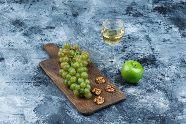 Wysoki kąt widzenia białych winogron, orzechów włoskich na desce do krojenia ze szklanką whisky, zielone jabłko na granatowym tle marmuru. poziomy