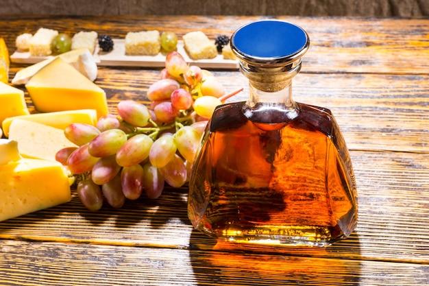 Wysoki kąt widzenia butelki alkoholu whisky na rustykalnym drewnianym stole z różnymi serami i winogronami z miejscem na kopię