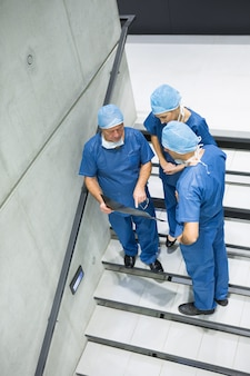 Wysoki kąt widzenia chirurgów omawiających prześwietlenie na klatce schodowej