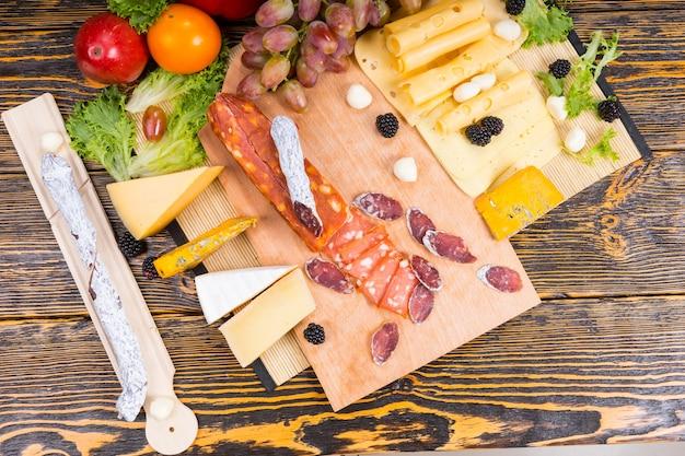 Wysoki kąt widzenia deski dla smakoszy z mięsem i serami z różnymi serami i przyozdobionymi owocami podanymi na rustykalnym drewnianym stole