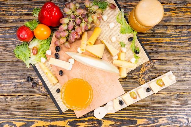 Wysoki kąt widzenia deski serów dla smakoszy ze świeżymi owocami, warzywami i przetworami na rustykalnym drewnianym stole