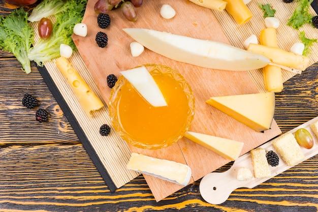 Wysoki kąt widzenia deski z serami i owocami dla smakoszy z naczyniem z przetworami owocowymi do maczania i różnorodnością klinów sera z miejscem na kopię na rustykalnym drewnianym stole