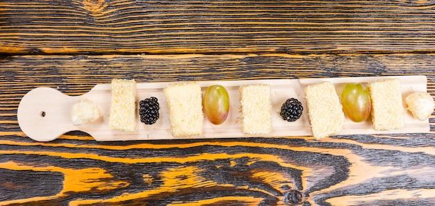 Wysoki kąt widzenia długiej deski serów dla smakoszy ze świeżymi owocami na rustykalnym drewnianym stole z słojami drewna