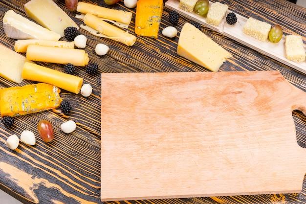 Wysoki kąt widzenia drewnianej deski otoczonej rozmaitymi serami dla smakoszy i świeżymi owocami na rustykalnym drewnianym stole z słojami drewna i miejscem na kopię