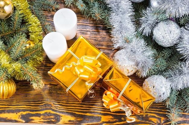 Wysoki kąt widzenia dwóch prezentów owiniętych w złoto z kokardkami obok białych świec słupkowych na rustykalnym drewnianym stole otoczonym wiecznie zielonymi gałęziami ozdobionymi blichtrowymi girlandami i kulkami