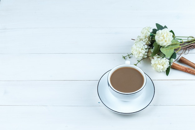 Wysoki kąt widzenia filiżankę kawy z kwiatami, cynamon na tle białej drewnianej deski. poziomy