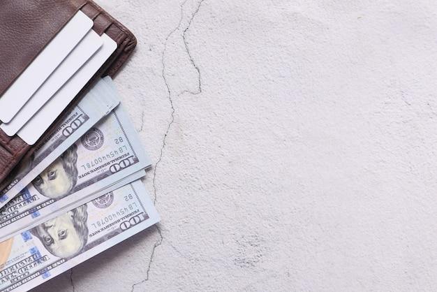 Wysoki kąt widzenia gotówki, karty kredytowej i portfela na białym tle