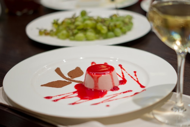 Wysoki kąt widzenia indywidualnej porcji pysznego deseru musowego zwieńczonego bogatym czerwonym syropem owocowym na stole restauracyjnym z lampką białego wina