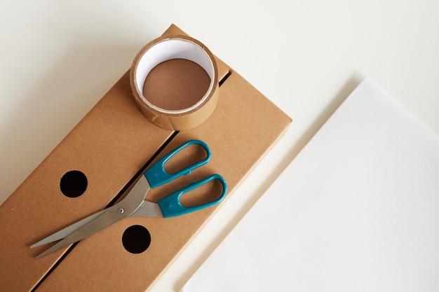 Wysoki kąt widzenia karton z taśmą klejącą i nożyczkami na nim na białym tle