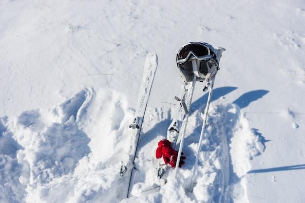 Wysoki kąt widzenia kasku i gogli z nartami, kijkami i czerwonymi rękawiczkami na powierzchni pokrytej śniegiem ze śladami stóp w słoneczny dzień z jasnym słońcem