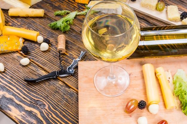 Wysoki kąt widzenia kieliszek białego wina na rustykalnym drewnianym stole otoczonym serami i owocami na wykwintną deskę serową
