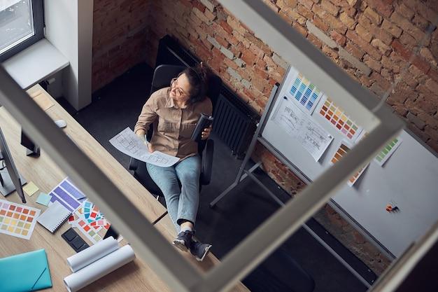 Wysoki kąt widzenia kobiecego projektanta wnętrz, patrzącego z boku na kawę lub herbatę