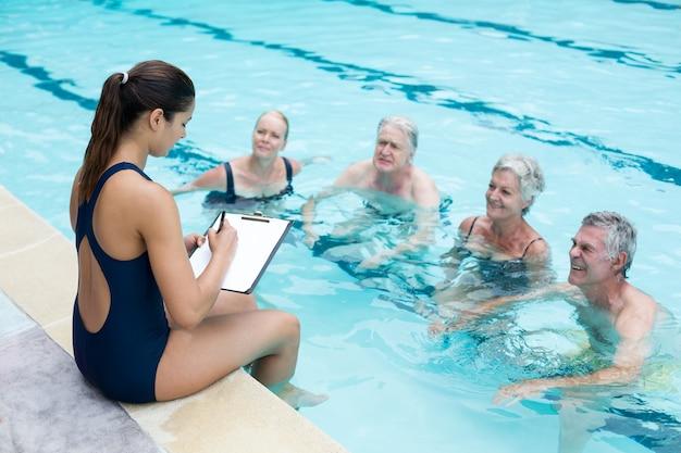 Wysoki kąt widzenia kobiet instruktor pisania podczas instruowania starszych pływaków przy basenie
