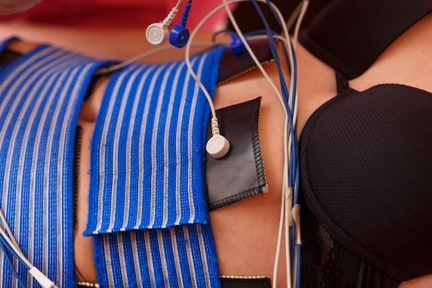 Wysoki kąt widzenia kobiety z elektrodami na brzuchu