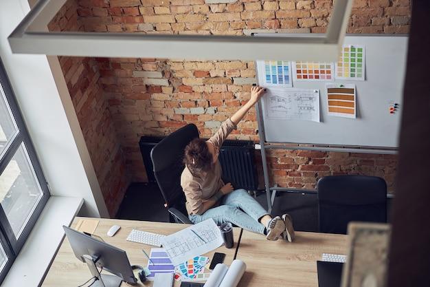 Wysoki kąt widzenia kreatywnej kobiety projektantki wnętrz, która podczas pracy dołącza plan na tablicy