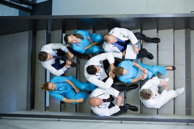 Wysoki kąt widzenia lekarzy i chirurgów siedzących na klatce schodowej