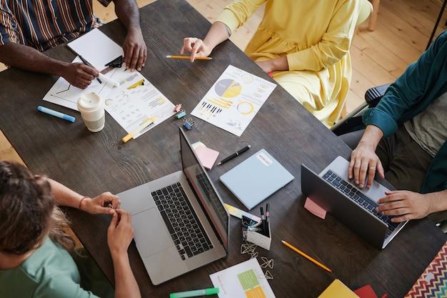 Wysoki kąt widzenia ludzi biznesu siedzących przy stole z dokumentami i komputerem oraz pracujących w zespole na spotkaniu biznesowym