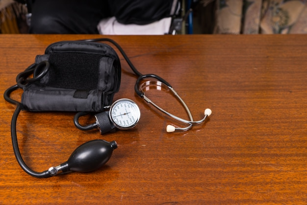 Wysoki kąt widzenia mankietu do pomiaru ciśnienia krwi i stetoskopu na drewnianym stole z miejscem na kopię