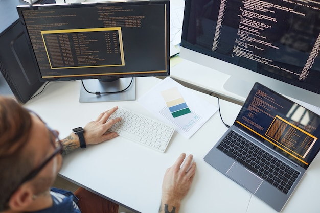 Wysoki kąt widzenia męskiego programisty piszącego kod podczas korzystania z wielu komputerów w biurze programistów it, kopiuj przestrzeń