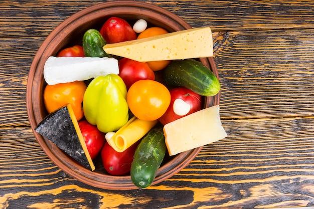 Wysoki kąt widzenia miski świeżo zebranych warzyw i klinów sera na rustykalnym drewnianym stole z drewna i miejsca na kopię