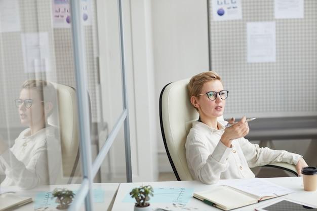 Wysoki kąt widzenia na nowoczesne krótkie włosy kobieta w okularach siedzi w dużym krześle w pracy, koncepcja szefa kobiet, kopia przestrzeń