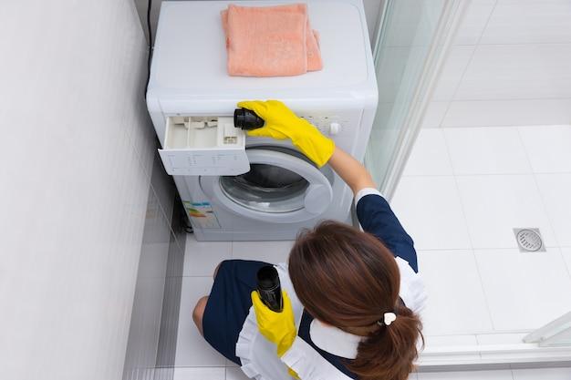 Wysoki kąt widzenia na samotną gospodynię przygotowującą małą pralkę ładowaną od przodu do załadunku prania