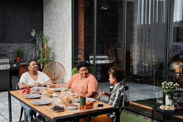 Wysoki kąt widzenia na szczęśliwą afrykańską rodzinę jedzącą razem kolację na tarasie na zewnątrz miejsca kopiowania