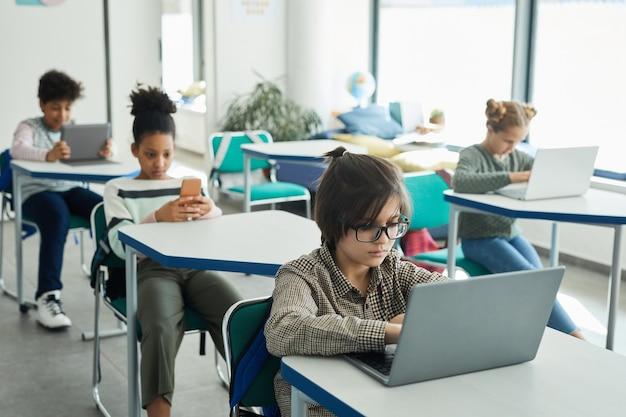Wysoki kąt widzenia na zróżnicowaną grupę małych dzieci korzystających z gadżetów podczas siedzenia przy biurkach w szkolnej klasie, miejsce kopiowania
