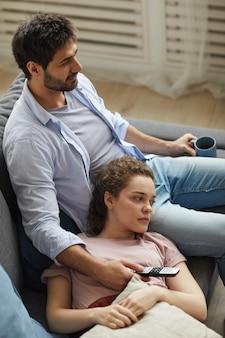 Wysoki kąt widzenia nowoczesnej pary oglądając telewizję razem, leżąc na kanapie w domu w przytulnym mieszkaniu, ciesząc się leniwym czasem