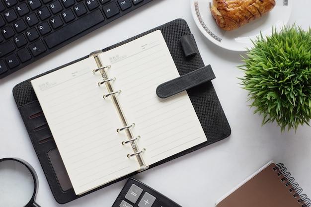 Wysoki kąt widzenia otwartego notatnika i biura stacjonarnego na białym tle