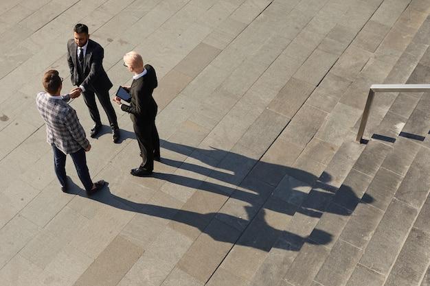 Wysoki kąt widzenia partnerów biznesowych, ściskając ręce, spotykają się na świeżym powietrzu w pobliżu schodów biurowca