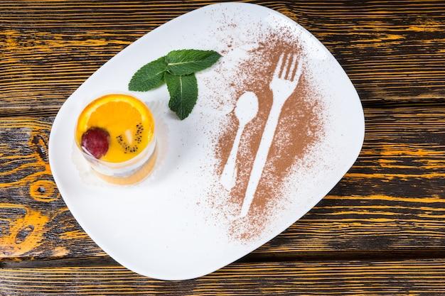 Wysoki kąt widzenia poszczególnych dekadenckich deserów owocowych podawanych na białym talerzu z ozdobami z liści mięty i konturami naczyń posypanych kakao na powierzchni drewnianego stołu