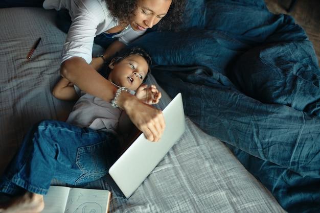 Wysoki kąt widzenia poważnej młodej kobiety o ciemnej karnacji przy użyciu komputera przenośnego w sypialni, podczas gdy synek czuje się znudzony, przeszkadzając jej w odległej pracy.