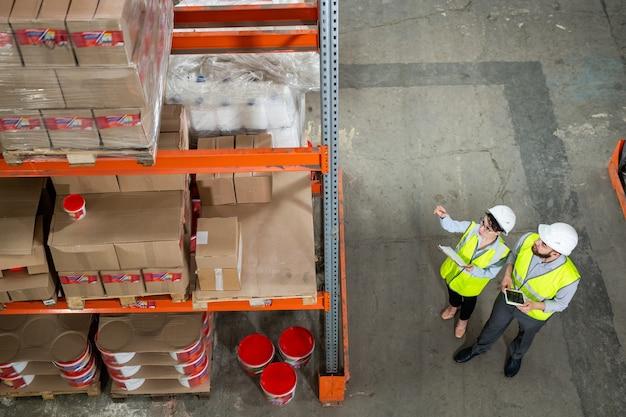 Wysoki kąt widzenia pracownika depozytu w kasku wskazującym na półkę podczas omawiania nowej dostawy z kierownikiem