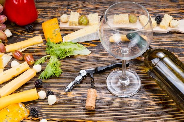 Wysoki kąt widzenia pustego kieliszka do wina i butelki białego wina na rustykalnym drewnianym stole wśród wyśmienitych serów i owoców