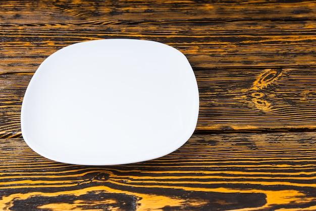 Wysoki kąt widzenia pustej gładkiej białej płyty ceramicznej na teksturowanym tle drewna z copyspace do umieszczenia jedzenia lub produktu