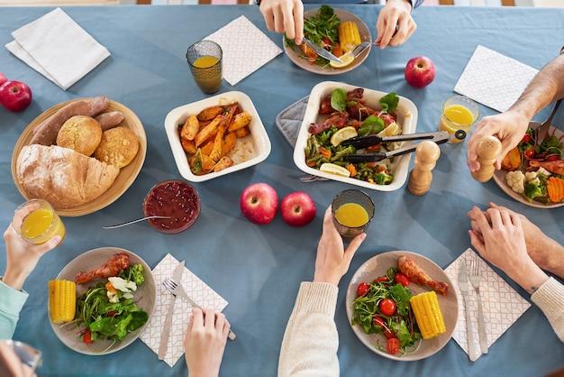 Wysoki kąt widzenia rodziny siedzącej przy stole i jedzącej sałatkę warzywną w porze lunchu
