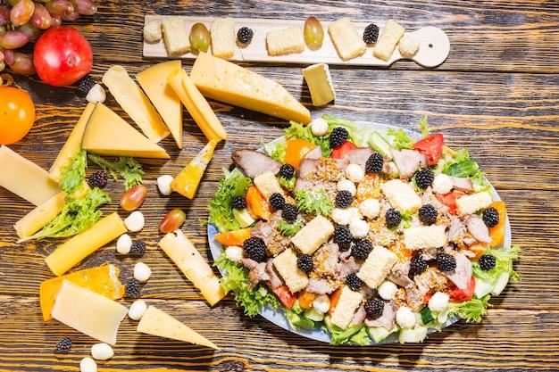 Wysoki kąt widzenia sałatki dla smakoszy ze świeżych warzyw, jeżyn, różnych serów i mięs z deską serów i składników na rustykalnym drewnianym stole