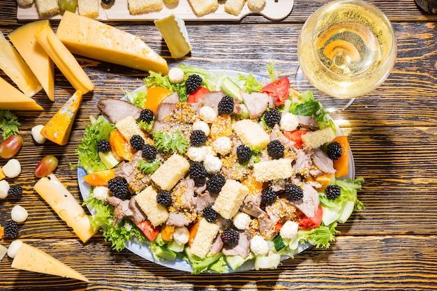 Wysoki kąt widzenia sałatki dla smakoszy ze świeżych warzyw, jeżyn, różnych serów i mięs z dodatkami i kieliszkiem białego wina na rustykalnym drewnianym stole