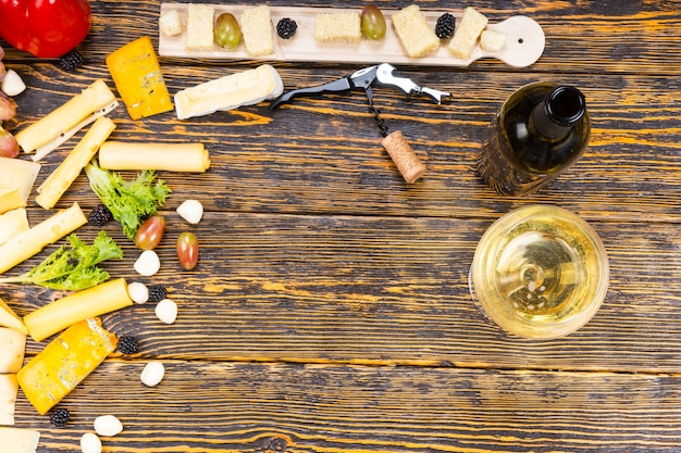 Wysoki kąt widzenia serów dla smakoszy i świeżych owoców z kieliszkiem białego wina i butelką na rustykalnym drewnianym stole z centralną przestrzenią kopii