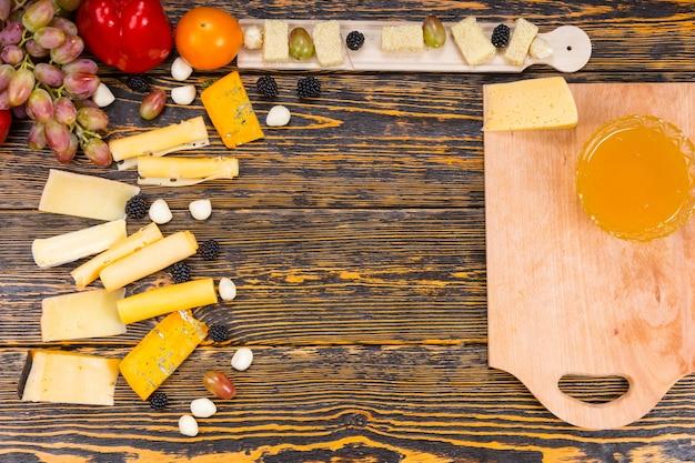 Wysoki kąt widzenia składników na deskę do serów - rustykalny drewniany stół z deską do krojenia i różnymi serami i owocami z miejscem na kopię w środku obrazu