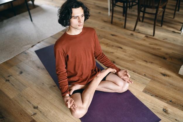 Wysoki kąt widzenia skupionego młodego mężczyzny o elastycznym ciele siedzącego w pozycji lotosu na macie, medytującego z otwartymi oczami, mającego uważne spojrzenie, koncentrującego się na jakimś przedmiocie, rozluźniającego ciało, zwalniającego