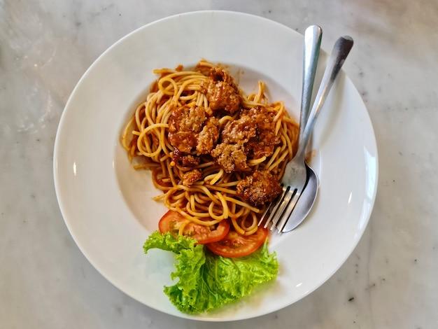 Wysoki kąt widzenia spaghetti z mieloną wieprzowiną na białym talerzu